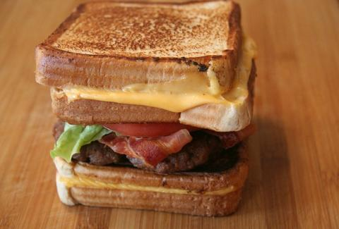 Burger between two grilled cheese sandwiches