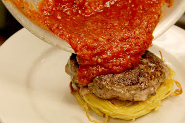 Marinara sauce is poured from the pan onto the Spaghetti Burger at PYT.