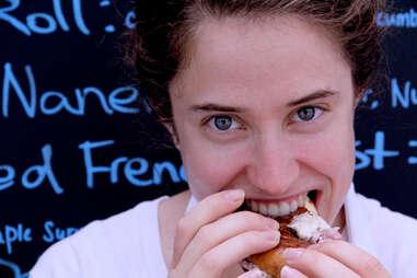 A girl eats a bagel from the Schmear It truck