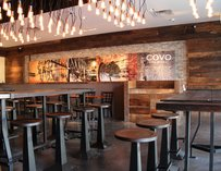 The interior at Covo with dark wooden tables and chairs.