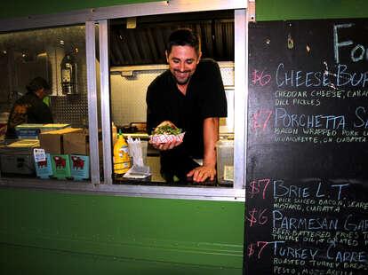 food truck man holding sandwich