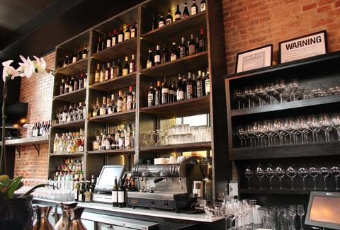The bar featuring a shelf filled with wines