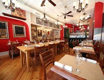 The very cozy interior at Flour & Water, with wooden tables and red walls.