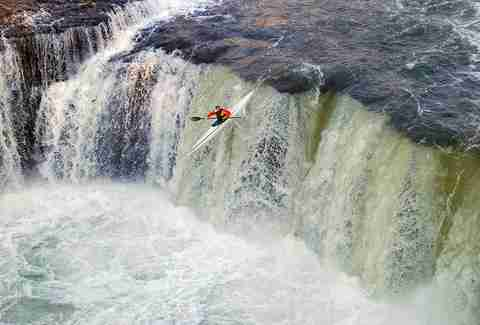 dane paddles over a waterfall