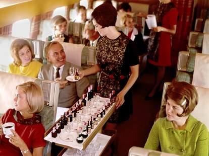 Flight attendant serving drinks on a plane