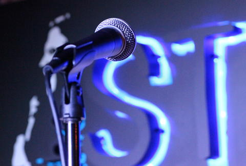 A close up of a microphone with a neon sign in the background