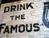 "Brick wall painted to read ""Drink the famous"""