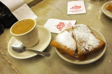 Fried dough with powdered sugar and coffee