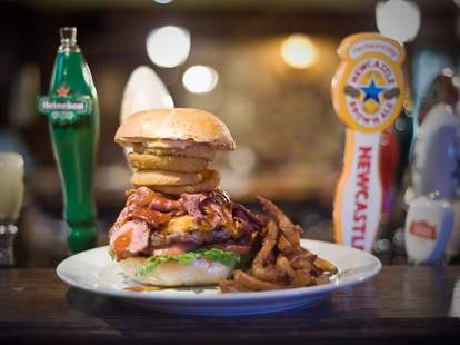 A giant burger with onion rings