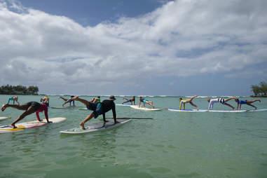 people doing yoga on surfboards