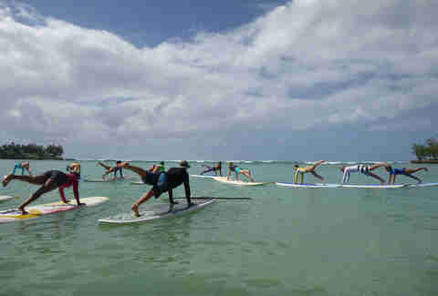 people doing yoga on surfboards
