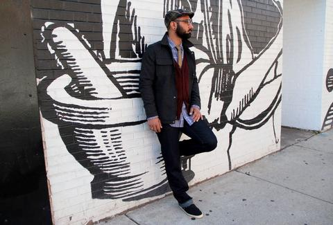 A stylish man leans against a graffiti wall.