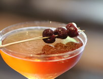 A cocktail garnished with cherries