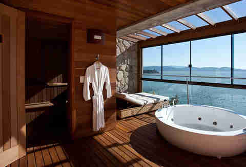 bathtub with robe and view of ocean
