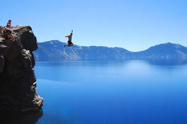 Another man jumping into water from a cliff